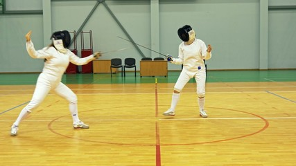 Two women on a fencing training