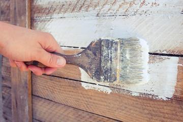 Female hand paint white paint boards old tassel