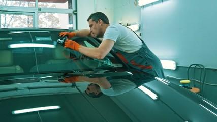Worker on a car wash applying anti rain coating on a windshield