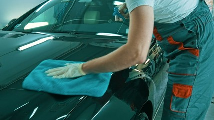 Worker wiping car on a car wash