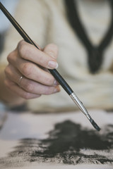 Closeup of female hand painting with brush