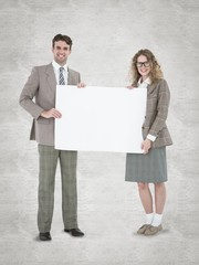 Hipster couple holding poster smiling at camera