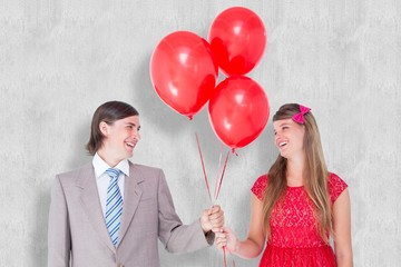 Composite image of smiling geeky couple holding red balloons