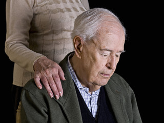 Old man, thoughtfully, with his wife's hand over his shoulder