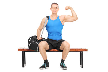 Muscular athlete showing his bicep seated on a bench