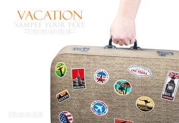 hand holding a retro suitcase with stickers isolated