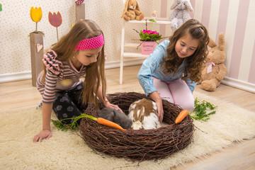 Easter - Little girls stroking the rabbits, the nest