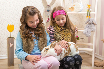 Easter - Little girls stroking the huge, live bunny