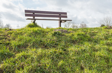 Wooden bench on the top of a Dutch dike in backlit