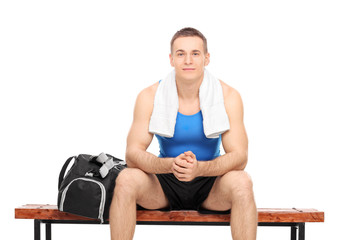 Young male athlete resting seated on a bench