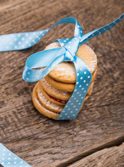 Sweet cookies tied with blue ribbon on wooden table