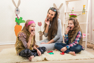 Easter - Mother and two daughters eat chocolate eggs