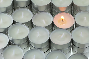 Closeup of Tea lights candle with one being lit