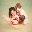 Happy family swimming together. Vintage filtered look.