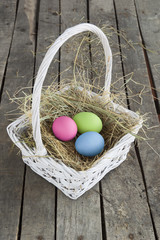Painted eggs on hay in white basket on wood