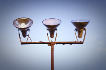 Three projectors of light against the sky background