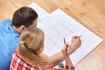 close up of couple with  blueprint at home