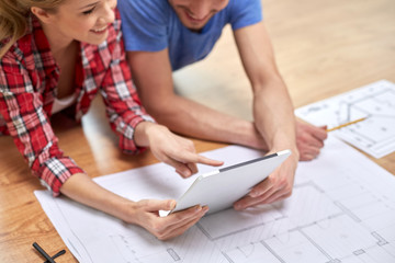 close up of couple with tablet pc and blueprint