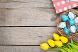 Fototapety Easter background with blue and white eggs in nest, yellow tulip