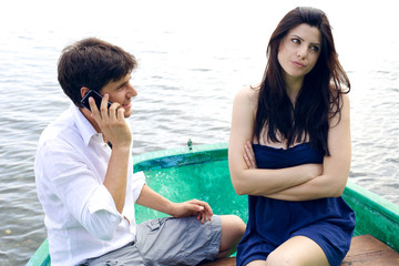 Unhappy woman with boyfriend smiling on the phone