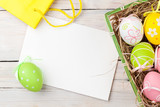 Fototapety Easter background with colorful eggs, yellow tulips and greeting