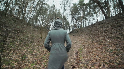 A girl in a grey coat walking up the path. Autumn landscape