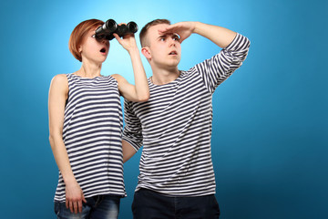 Man and woman in striped clothing looking through binoculars