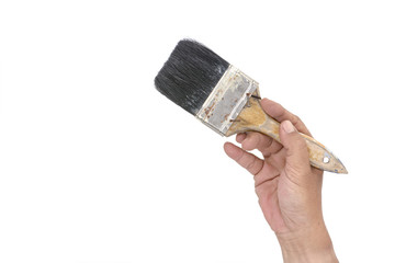 Hand holding an old dirty used paint brush isolated on a white b