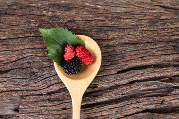 mulberry fruit in the wooden spoon on wood plate