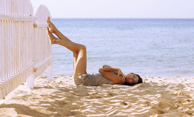 Attractive girl lying on the sand by sea. Sunny day.