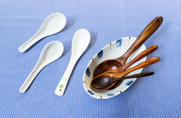 Set of Wooden Spoon in White Bowl with Three Ceramic Spoon on Bl
