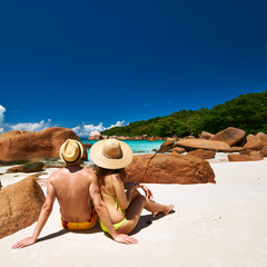 Couple sitting on a beach at Seychelles