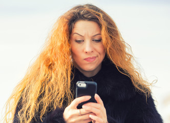 upset sad skeptical unhappy woman texting on mobile phone