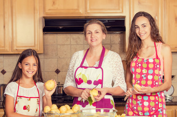 happy, smiling mother and her daughters cooking dinner