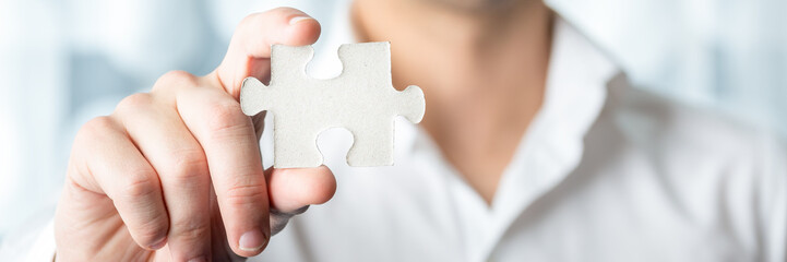 Businessman Holding Jigsaw Puzzle Piece