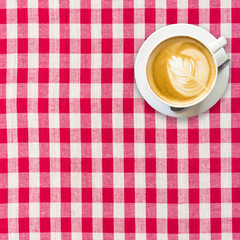cappuccino coffee on white and red checkered background close up