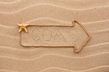 Arrow made of rope and sea shells with the word Goa on the sand