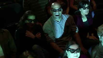 Audience jumps back at a dramatic event during a 3D movie screening.  Camera moves on a jib and moving images are projected on the people.