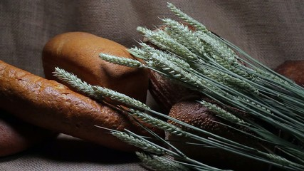 Different types of bread with wheat spikelets on sackcloth