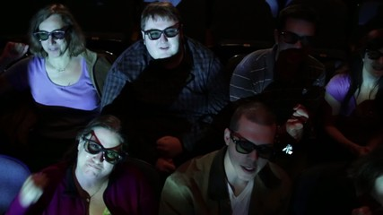 Audience gets excited at a 3D movie screening.  Camera moves on a jib and moving images are projected on the people.