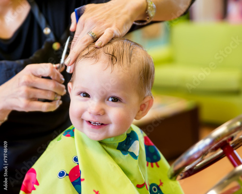 Happy toddler child getting his first haircut - 79748409