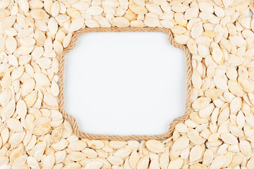 Figured frame made of rope with  pumpkin seeds  lying on a white