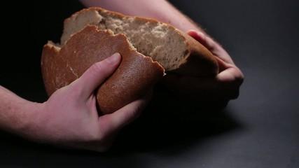 Male hand break brown bread