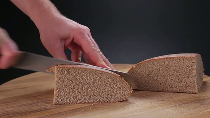 Cutting black bread of slices.