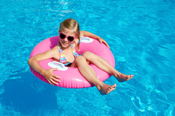 Girl resting in the swimming pool at the resort