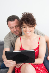 Portrait of a smiling couple using digital tablet