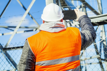 Engineer filmed with tablet PC at outdoors near metal structures