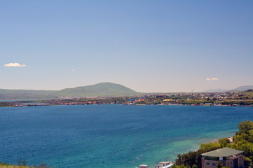 Shore of Sevan lake with houses and mountains