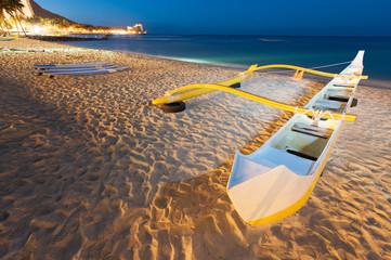 Outrigger canoe sits on the Waikiki beach
