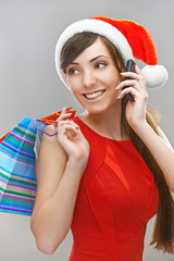 smiling woman in Santa Claus clothes with phone